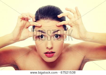 Woman checking her wrinkles on her forehead.