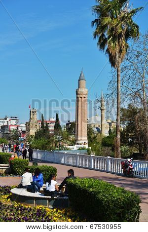 ANTALYA, TURKEY - MARCH 26, 2014: People resting in the park against Yivli minaret. Built in XIV century, this 38 metres tall minaret is now the symbol of the city
