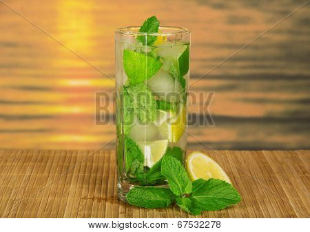 Glass with a mojito, lime and spearmint leaf