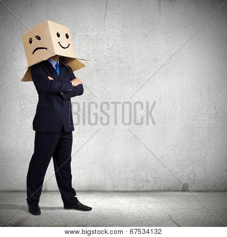 Businessman wearing carton box with smileys on head