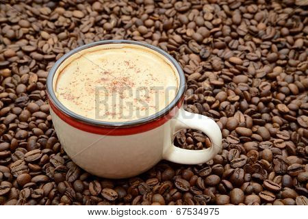 cup of coffee with cinnamon on a coffee beans background