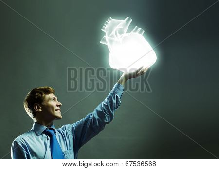 Young businessman holding human 3d heart in palm