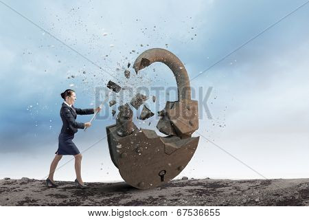 Young angry businesswoman crashing stone lock with hammer