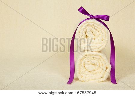 Two towels roll decorated with ribbon