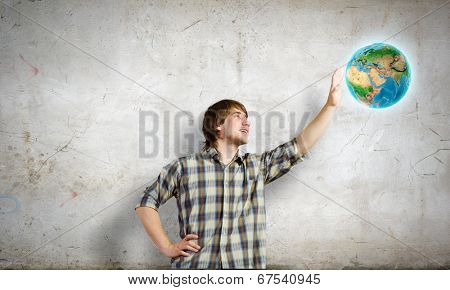Young man touching image of Earth planet. Elements of this image are furnished by NASA