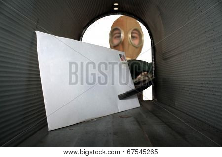 A unidentifiable person in a Gas Mask retrieves or sends mail from their mail box with an extension grabber so they do not touch the mail with their hands, for fear of disease or anthrax or more.