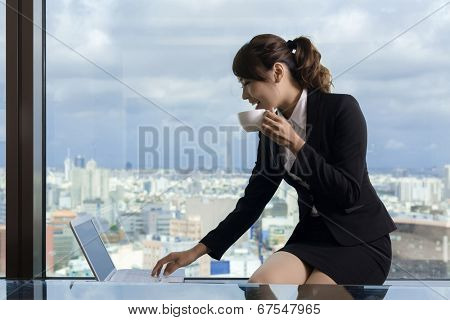 Asian business woman work and take a cup of coffee in hotel room.