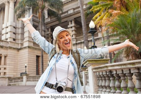 cheerful tourist arms up in front of historical building