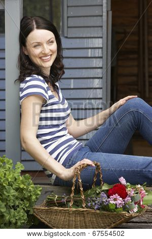 Woman sitting  on veranda with flowers