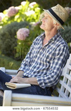 Mid age man reading in garden