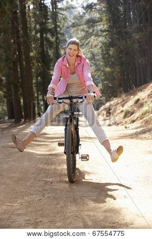 Woman freewheeling down country lane