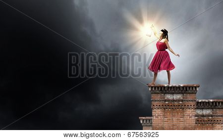 Young woman in red dress with lantern