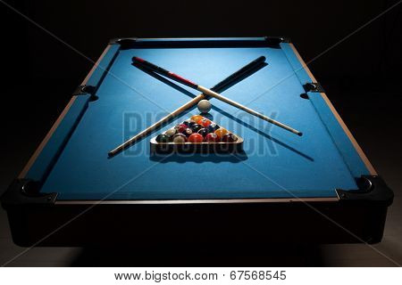 Pool equipment ready for a frame with crossed wooden cues, racked balls and a cue ball on a blue baize table surrounded by darkness