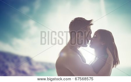 Silhouettes of the head and shoulders of a romantic young couple kissing backlit by the sun with a coastal backdrop