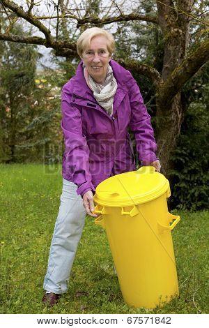 Woman With Dustbin In Garden