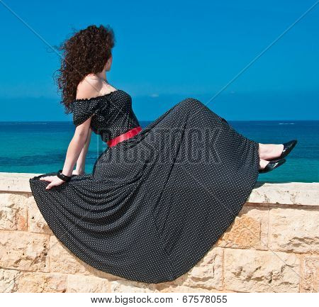 Girl In A Beautiful Long Dress Against The Sea