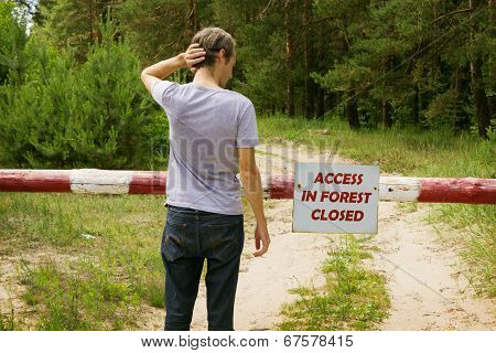 Man Stands In Front Of A Barrier In The Forest