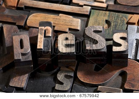 press written with vintage letterpress printing blocks on random letters background