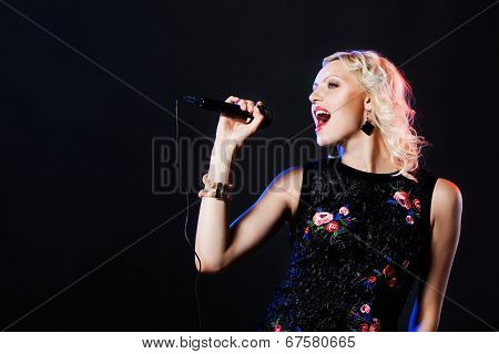 Beautiful blonde singing woman with microphone. Singer. Karaoke song