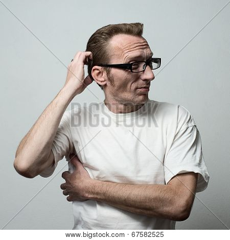 Unshaven Man in deep thought itching his head