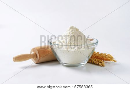 flour in the glass bowl with wooden rolling pin and wheat ear