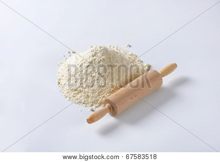 heap of flour with wooden rolling pin