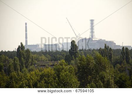 Forest and Chernobyl nuclear reactor in the background, it was covered with sarcophagus and abandoned after nuclear disaster in Chernobyl at 26.04.1986 (taken from Pripyat)