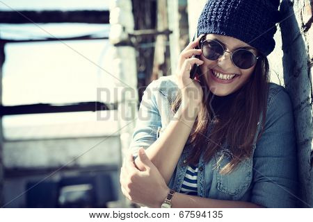 Girl having fun outdoors calling smart phone, lifestyle. Toned.