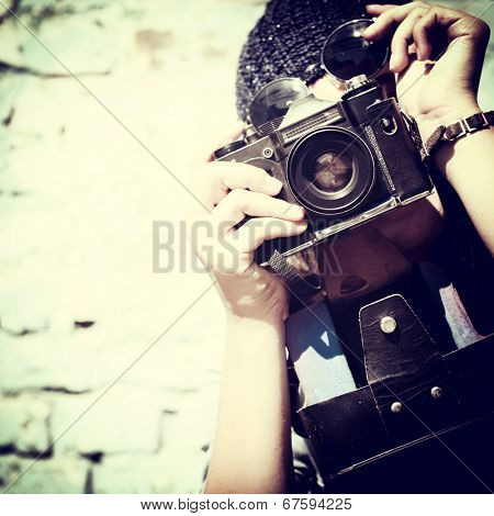 urban girl has fun with vintage photo camera outdoor near grunge wall, image toned.