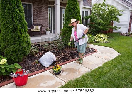 Senior Lady Preparing The Garden For Flowers