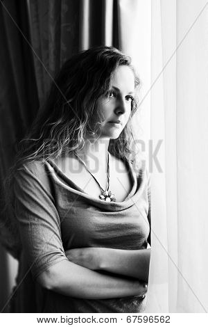 Sad beautiful woman with long curly hairs looking out window