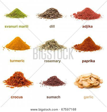 Heap ground Svanuri marili, dill seed, adjika, turmeric, rosemary, paprika, saffron, sumach and garlic isolated on white background