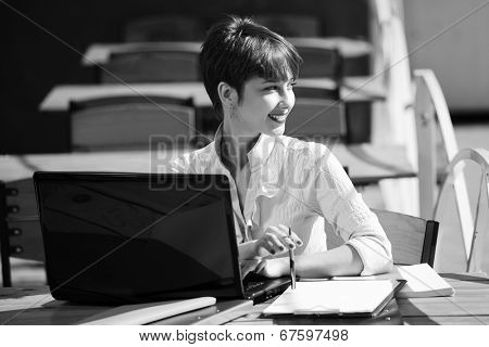 Young business woman using laptop at sidewalk cafe