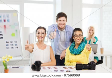business, education, photography, office and startup concept - smiling creative team with photocamera in office showing thumbs up