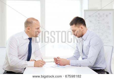 business and office concept - two serious businessman with papers in office