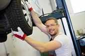 stock photo of bearings  - Mechanic checking wheel bearings in a car workshop - JPG
