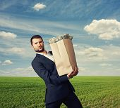 image of heavy bag  - young businessman holding heavy paper bag with money over blue sky and green field - JPG