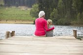 image of granddaughters  - Grandmother and granddaughter sitting on a jetty - JPG