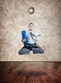 picture of levitation  - Businessman holding yoga mat and doing Levitation in lotus pose in the yoga hall with clock on the wall - JPG