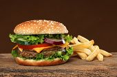 pic of hamburger  - Tasty hamburger and french frites on wood background - JPG