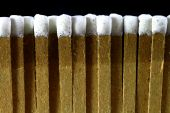 stock photo of sulfur tip  - closeup of a row of paper white tipped matches on a black background - JPG