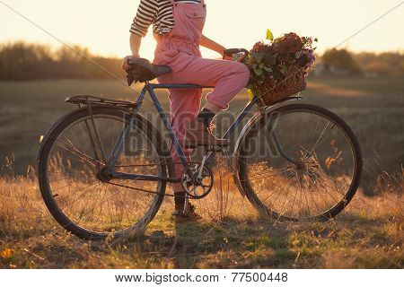 Oldfashioned Girl And Bike At Sunset