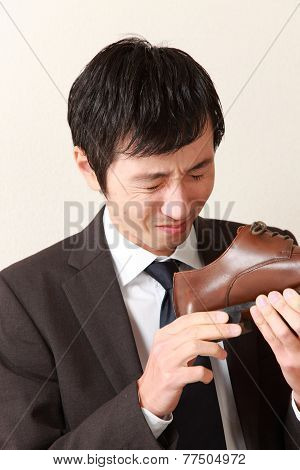 businessman smells one of shoes