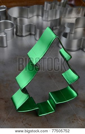 Closeup of a green metal Christmas tree cookie cutter on a baking sheet with random cutters in the background. The shot is primarily monochromatic except for the green object in the foreground.