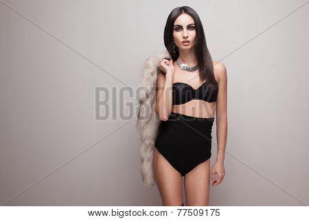 Walking Fashionable Model In Black High Shorts And Bra.  Holding Fur Vest