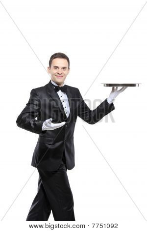A young butler carrying a tray