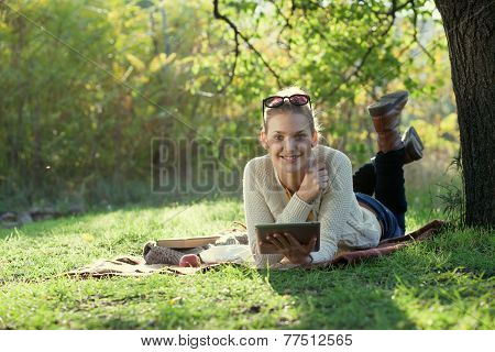 Smiling Woman Using Tablet Computer Outdoors