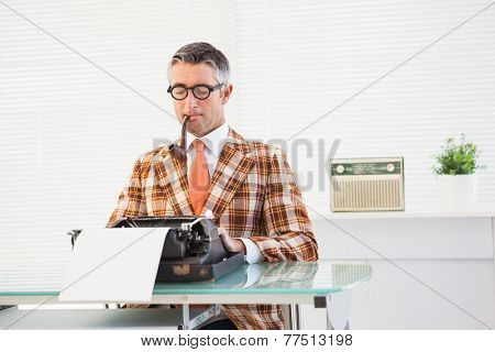 Retro man typing on typewriter in his office