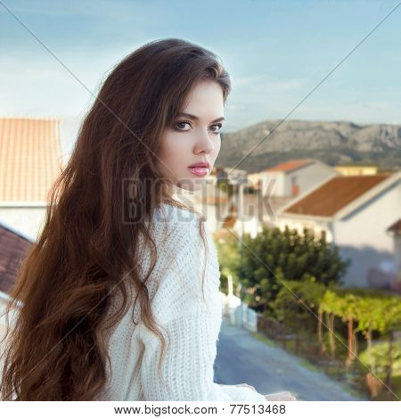 Attractive Brunette Girl With Healthy Long Wavy Hair Standing On Balcony Looking Away
