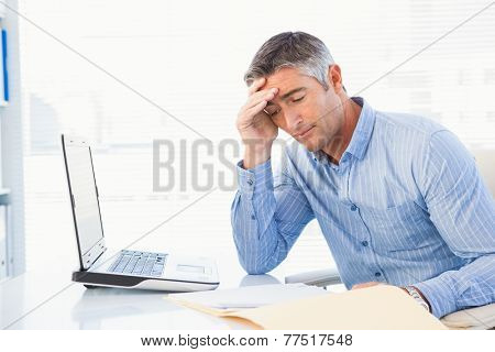 Concentrated man reading a document attentively in his office